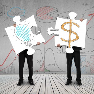 Two men connecting puzzles for idea is money concept on wooden floor